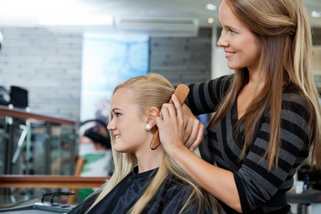 Side view of hairdresser combing hair of female customer before haircut photo