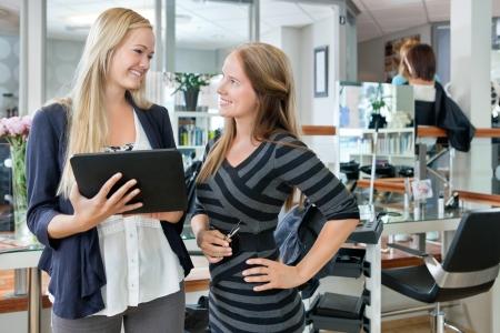 estilista: Feliz clienta joven que busca en la peluquer�a, mientras que la celebraci�n de tableta digital
