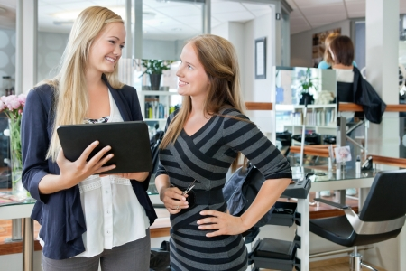 stylist: Happy young female customer looking at hairdresser while holding digital tablet