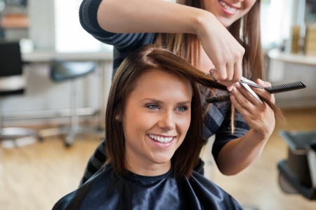 salon: Happy young woman getting a new haircut by hairdresser at parlor
