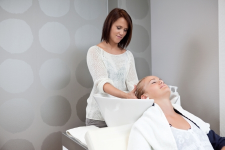 Relaxed young woman receiving head massage at hair salon photo