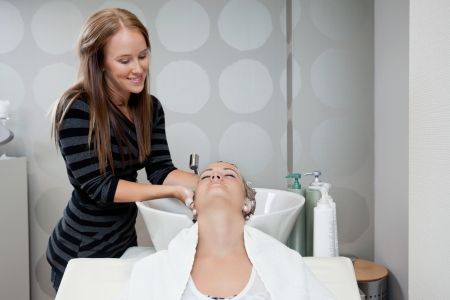 Pretty female beautician washing customer s hair before a haircut at beauty salon photo