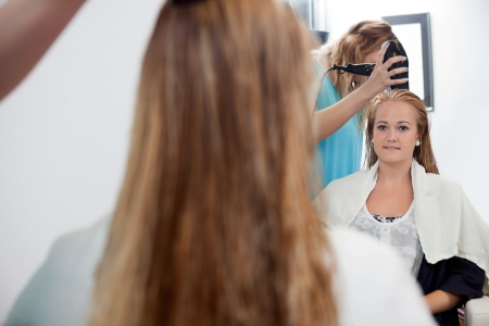 sylist: Mirror reflection of beautician drying long blond hair with hair dryer at parlor