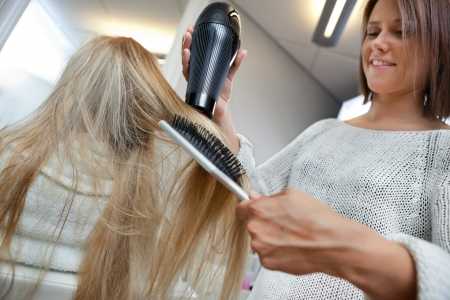 Low angle view of hairdresser drying long blond hair with blow dryer and brush photo