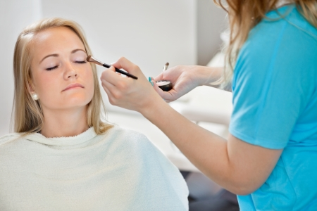 Midsection of beautician applying eye shadow to young woman at parlor photo