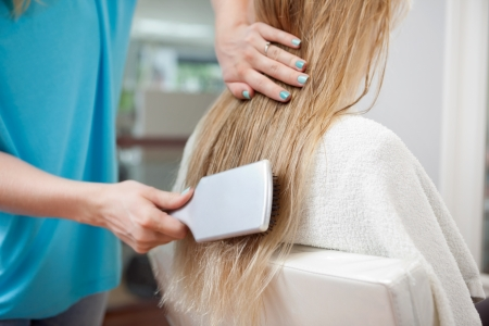 sylist: Beautician combing long blond hair of female customer with brush at parlor