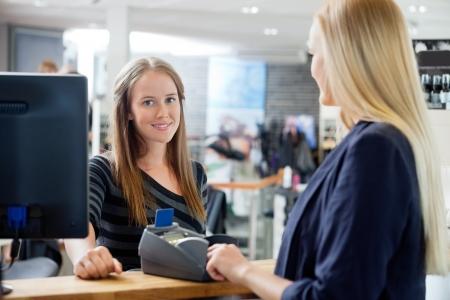 contadores: Retrato de mujer joven empleado de ventas de pie por el contador con el cliente en el sal�n de