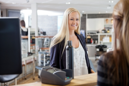 checkout stand: Young blonde woman standing by cash counter at hair salon