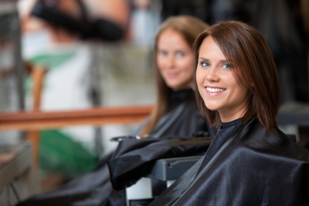 Portrait of young woman smiling with female customer in background at parlor Stock Photo - 14508228