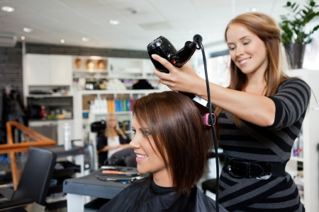 beauty parlor: Beautician blow drying woman s hair after giving a new haircut at parlor