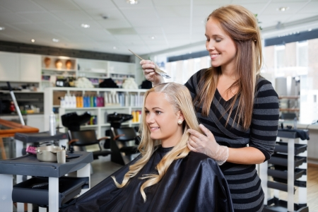 apply: Young woman having her hair dyed by beautician at parlor
