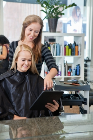 Mirror reflection of hairdresser pointing at digital tablet while female customer holding it photo