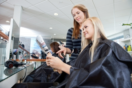 Hairdresser pointing at magazine held by female customer in parlor photo
