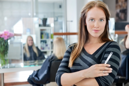 Portrait of a confident female owner of parlor standing arms crossed with people in background Stock Photo - 14508190