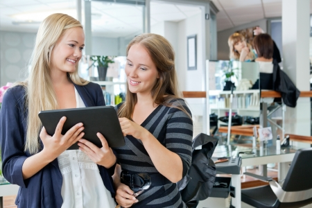 Young female customer holding digital tablet while standing with hairdresser at parlor photo