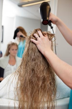 Beautician blow drying woman s hair at parlor photo
