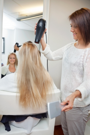 Pretty beautician blow drying female s long blond hair at parlor photo