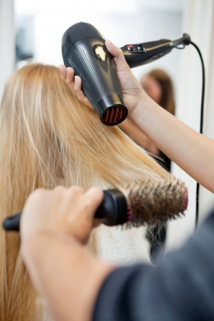 blow: Primo piano di mani parrucchieri di essiccazione lunghi capelli biondi con phon e spazzola rotonda