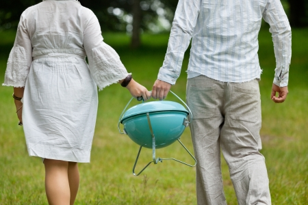 leisureliness: Back view of a couple in casual wear walking with a portable barbeque on an outdoor picnic