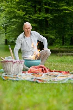 leisureliness: Mature man in casual wear with a flaming portable barbecue at an outdoor picnic