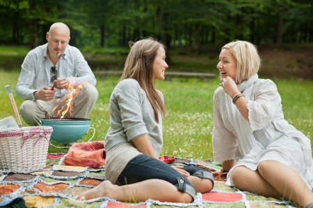 picnic blanket: Friends visiting and preparing a barbecue for outdoor picnic