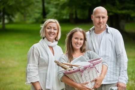 leisureliness: Portrait of a cute young female holding picnic basket while standing with parents Stock Photo