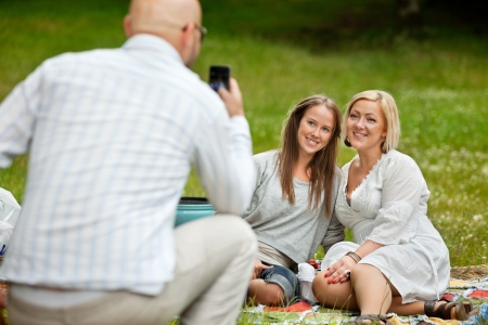 Rear view of man taking picture of friends with cell phone Stock Photo - 14508134