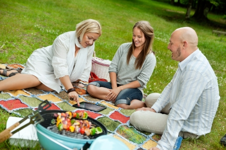 Group of friends looking at pictures outdoors in park photo