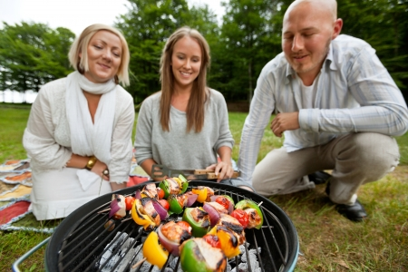 Three friends cooking shish kebabs over portable barbecue photo