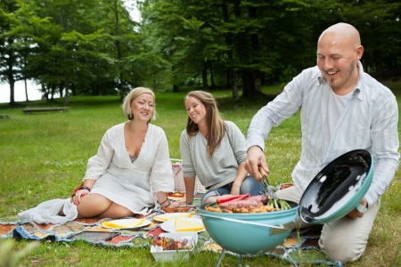 Happy Caucasian friends cooking barbeque meal at an outdoor picnic in forest park photo