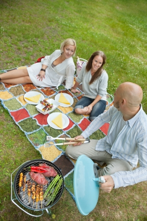 High angle view of man cooking meat on portable barbeque while looking at friends photo