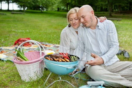 Mature couple in casual wear cooking meat and chilies on a portable barbecue at an outdoor picnic in forest park photo