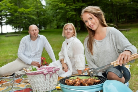 Group of friends with bbq picnic in park photo