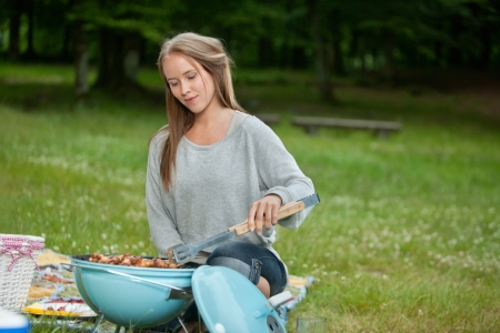 leisureliness: Cute young woman in casual wear cooking food on a portable barbecue in park at weekend outing