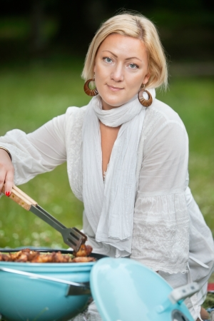 Portrait of an attractive woman in casual wear cooking food on portable barbecue photo