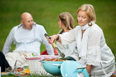 Woman cooking food on a portable barbecue while man and girl sit in background Stock Photo - 14508137