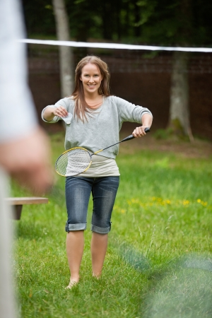 Happy young female in casual wear with racquet and birdie ready to serve photo