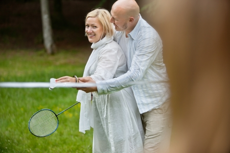 Portrait of mature couple in casual wear playing badminton together on a weekend outing photo