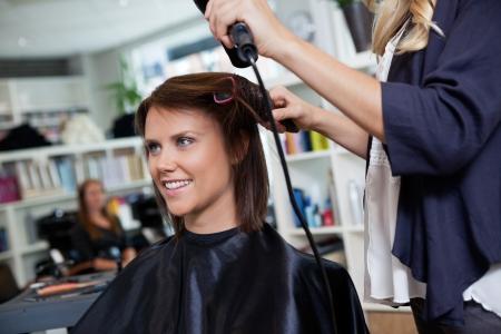 secador de pelo: Mujer feliz joven que consigue la fijación del cabello por esteticista después del nuevo corte de pelo Foto de archivo