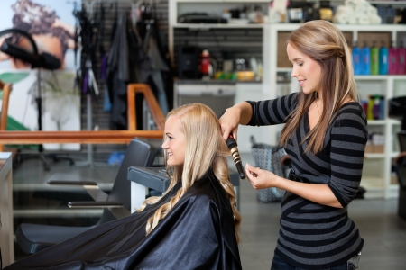 salon hair: Side view of young stylist curling woman s hair giving a new hairstyle at hair salon Stock Photo