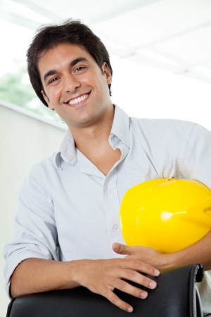 project manager: Portrait of happy young male architect holding yellow hardhat while standing by office chair Stock Photo