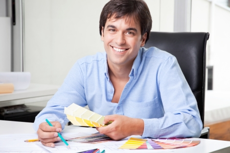 Male interior designer at office with color swatch  photo