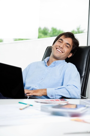 designer chair: Portrait of happy young male interior designer with laptop sitting in office chair