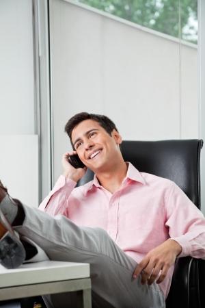 answering phone: Joven empresario respondiendo a la llamada de tel�fono en la oficina con las piernas sobre el escritorio Foto de archivo