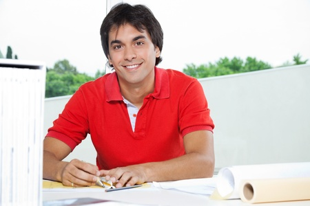 Portrait of young male architect smiling while working on a blueprint photo