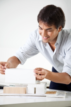 scale model: Young male architect preparing a model house on desk Stock Photo