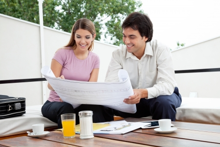 Male architect discussing house plans with female photo