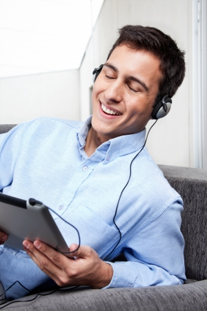Relaxed young man on couch listening music   Stock Photo - 14838421