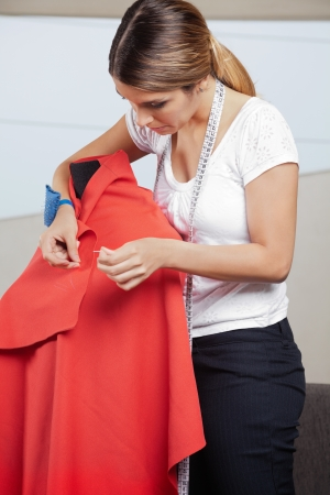 Young female fashion designer adjusting pins on a red fabric draped on mannequin photo