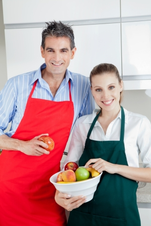 Happy couple standing in kitchen with bowl of fruit photo